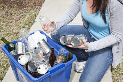 Low section of woman putting plastic and metal containers in recycling bin.
